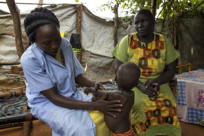 A community health worker examining a child