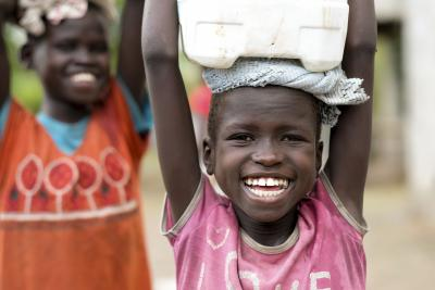 A girl is carrying water in a bucket on her head