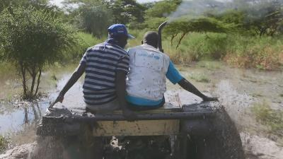Two people in a tractor on a muddy road