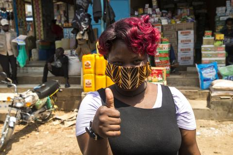 A woman wearing mask is giving thumps up.
