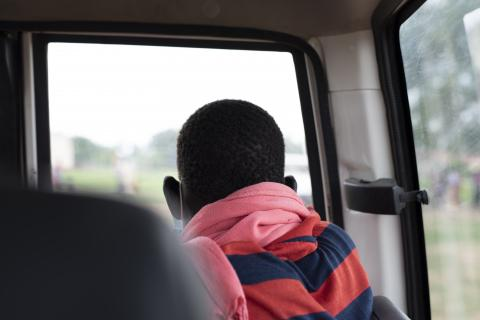 A boy looking out the window in a car