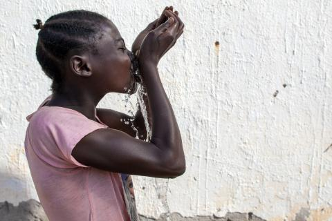 A girl drinking water from her hands