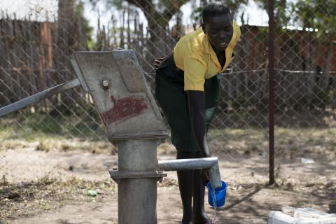 A girl is getting water from a pumping station using a cup