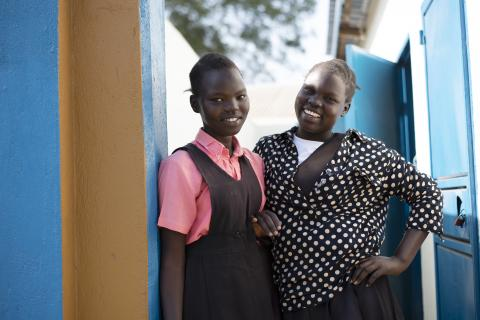 two girls standing outside a latrine