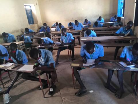 Children sitting in class taking their exams