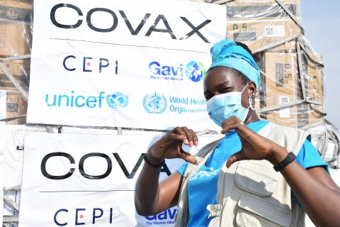 A UNICEF staff forming a heart with her finger