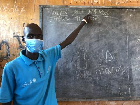 A man in a UNICEF shirt and mask stands at a blackboard