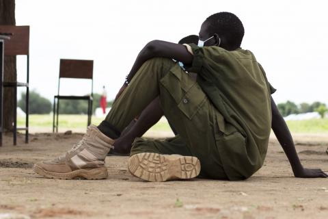 A child soldier is sitting on the ground
