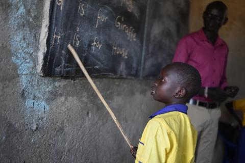 A boy standing next to the blackboard