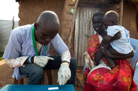 (Left) Dau Kiir, one of 70 trained Community Based Distributors (CBD), conducts a malaria test during a home visit to Lina Abui's home on her son, who is suffering from a severe case of malaria.