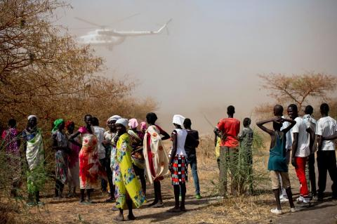 Community members watch as a World Food Programme helicopter lands, with emergency food and medical supplies