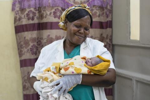 A midwife is holding a newborn