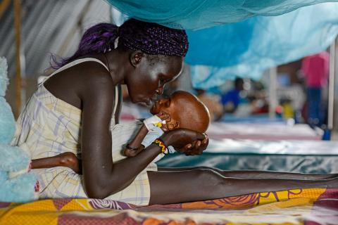 Eliza, 28, kisses her baby, Jal Puok, 1, who is suffering from severe acute malnutrition