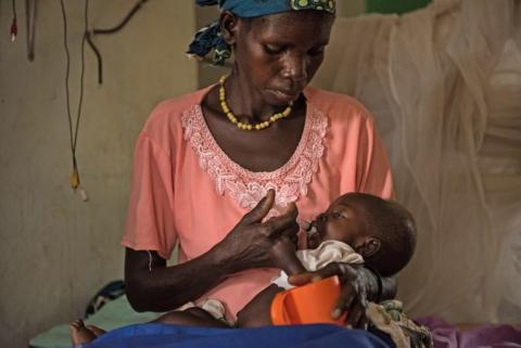 A mother holds her baby son in her arms and feeds him therapeutic food.