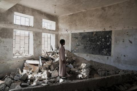 A boy stands in the rubble of a classroom, Yemen