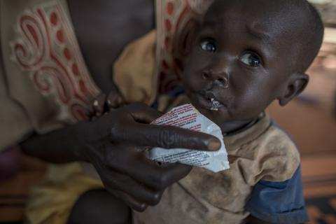 A boy is given ready-to-use therapeutic food