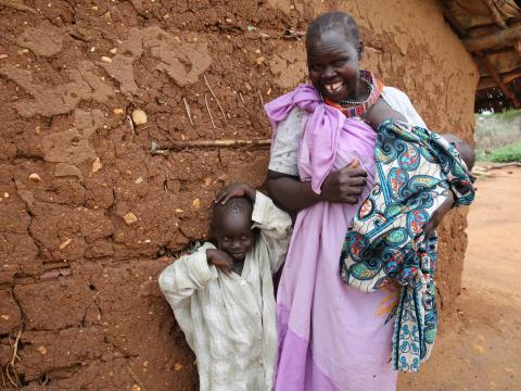 A mother stands with her son and new baby outside their home, South Sudan