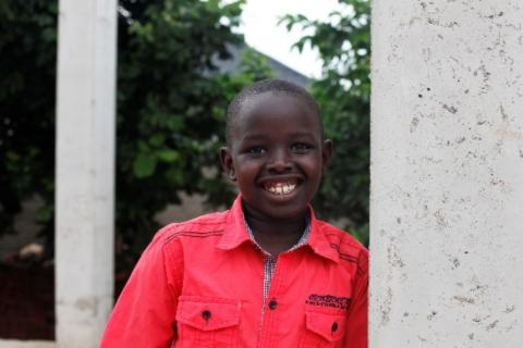 Kukuac, 8 years, poses for a photo outside his home in Juba, South Sudan.