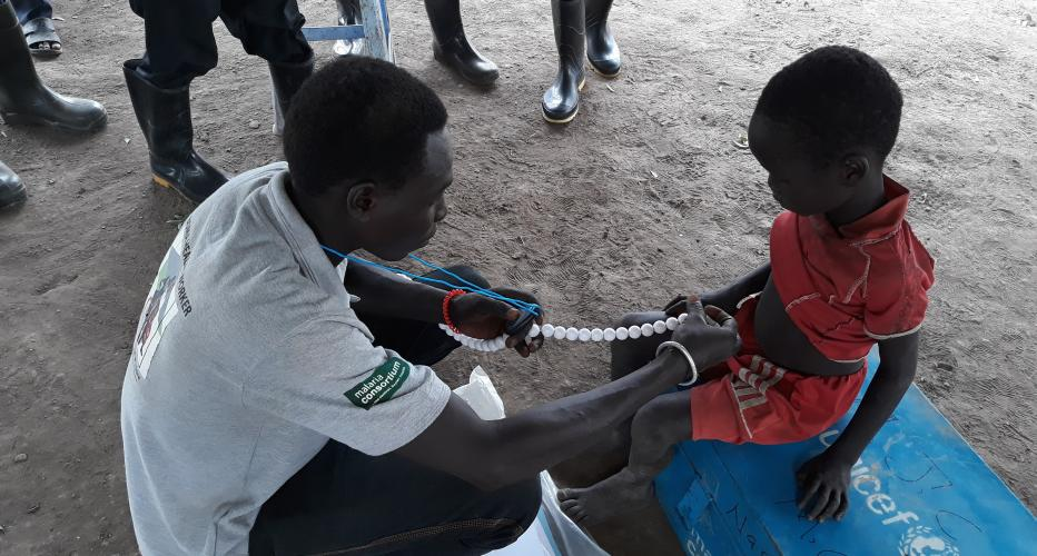 A man is examining a boy using beads and a timer