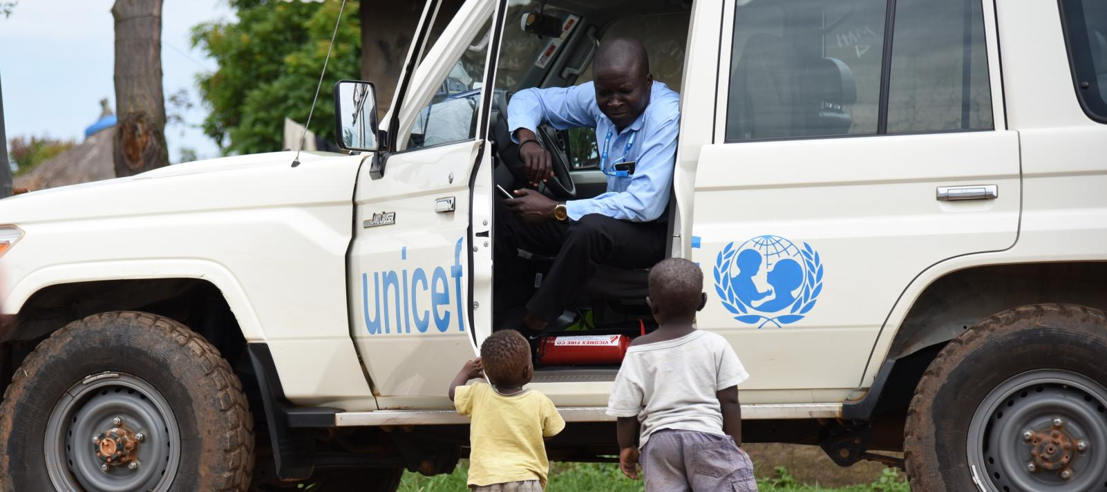 To children are approaching a UNICEF car and driver
