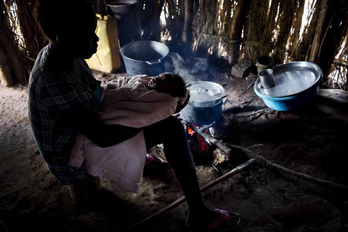 Esther, 18, holds her baby as she prepares food inside her home