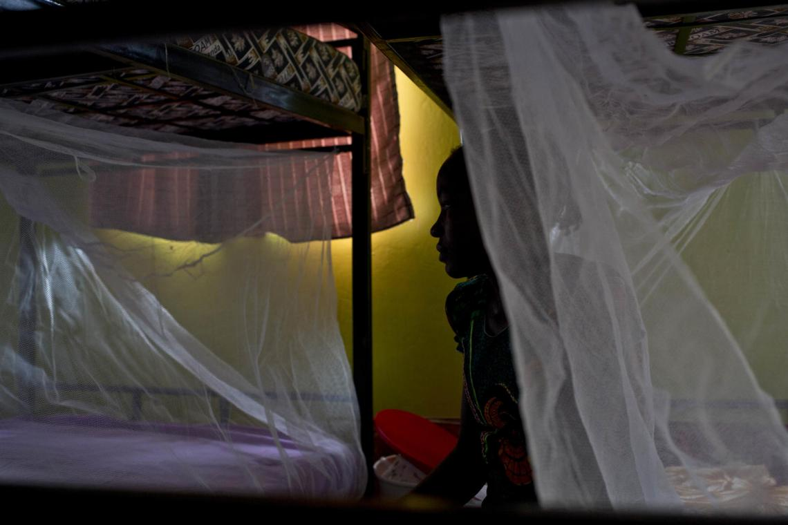 Rose, 17, sits on a bed half behind a mosquito net