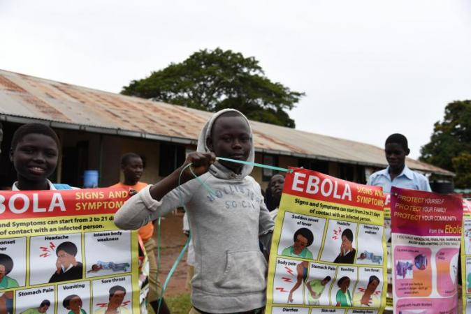 A girl is holding up a posted with important Ebola messages in a school in Yei.