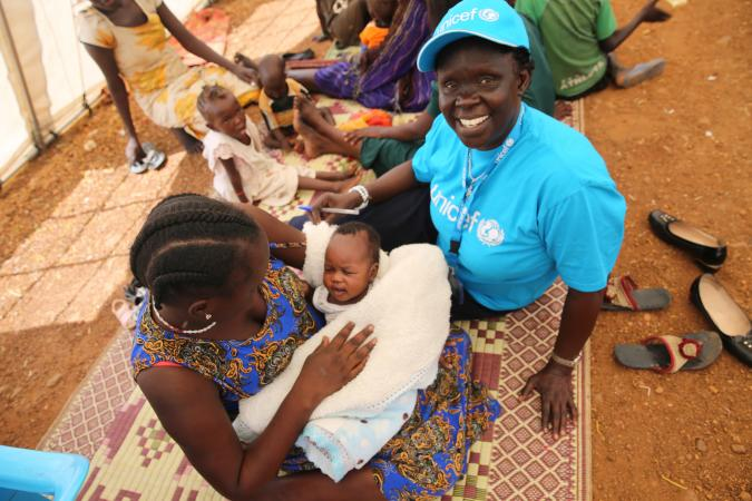 A mother and her newborn together with UNICEF staff member Cecilia Aldo
