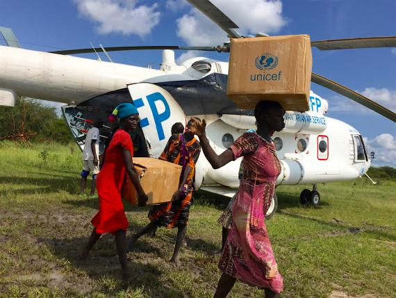 Women offloading UNICEF supplies from a WFP helicopter