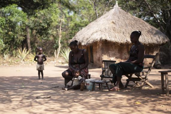 A village setting where women are plating hair