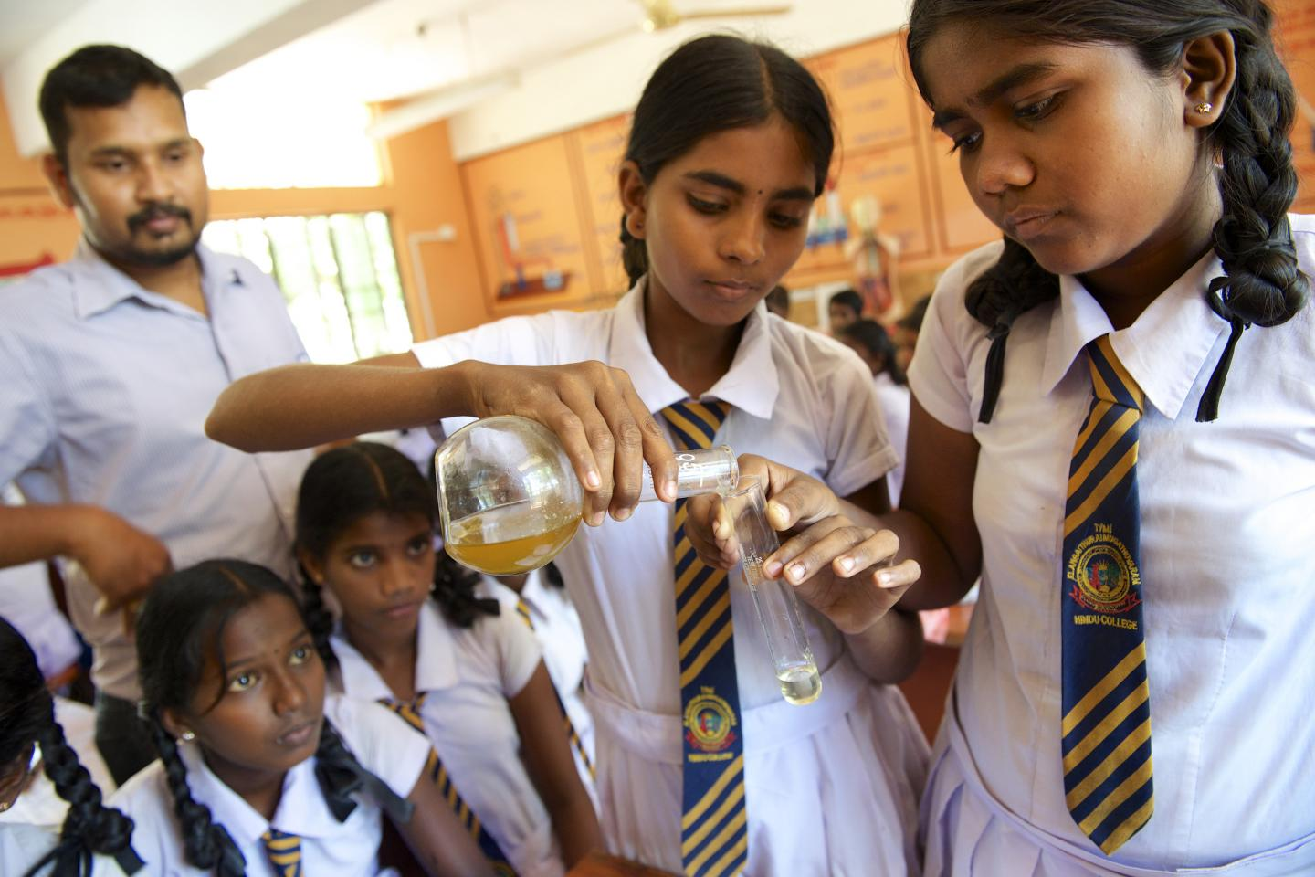 Adolescent schools girls carrying out a chemistry experiment.