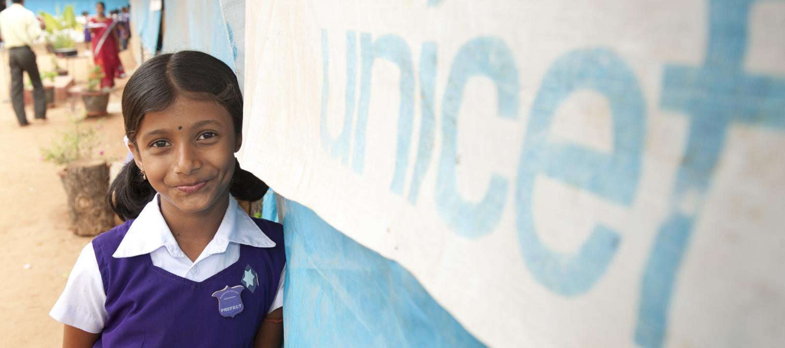 Girl standing next to a UNICEF banner