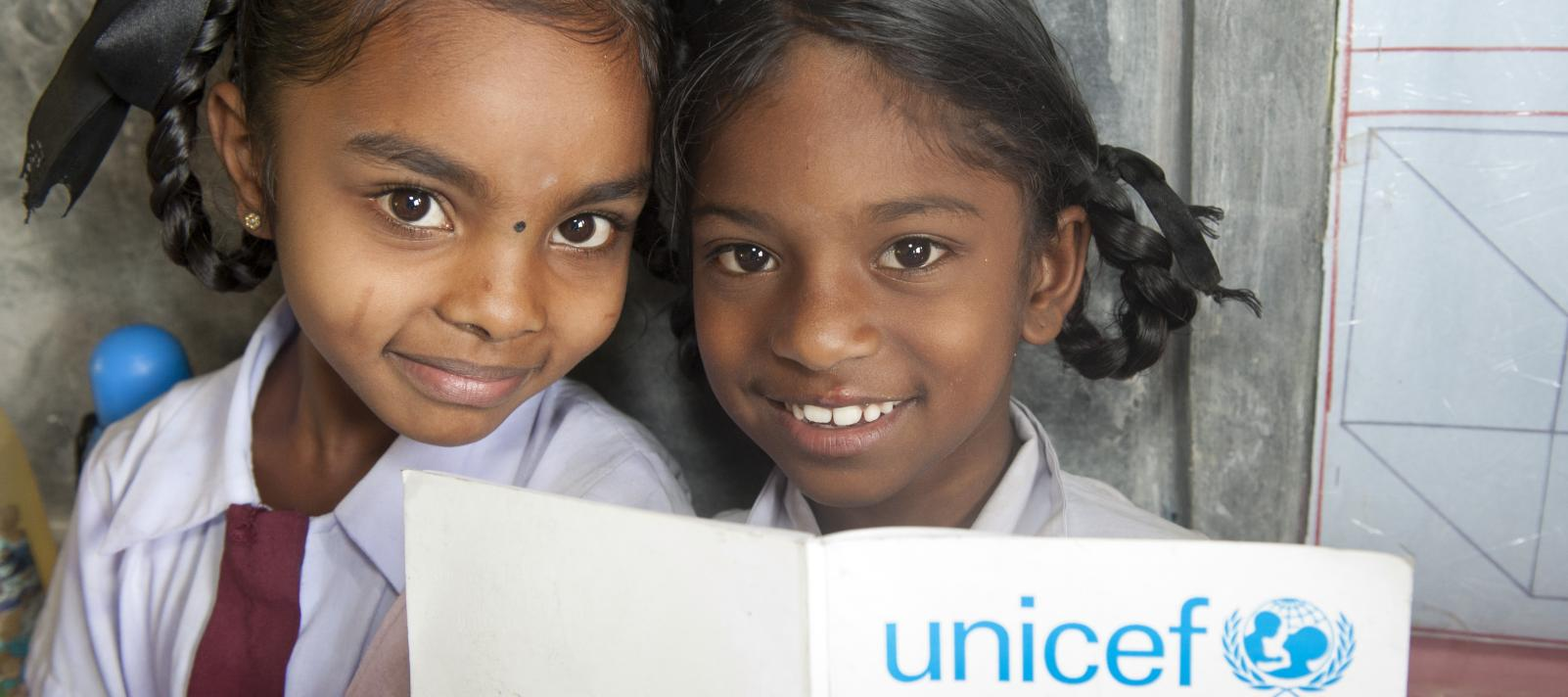 two girl's with a unicef book