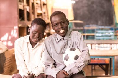 Two boys in a classroom holding a soccer ball