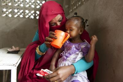a woman feeds her daughter plumpy nut paste,