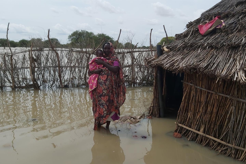 Frau, die ihr Baby im Wasserbecken neben Haus hält
