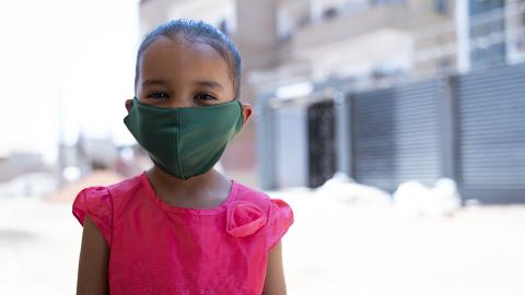 Girl in pink shirt wearing green face mask