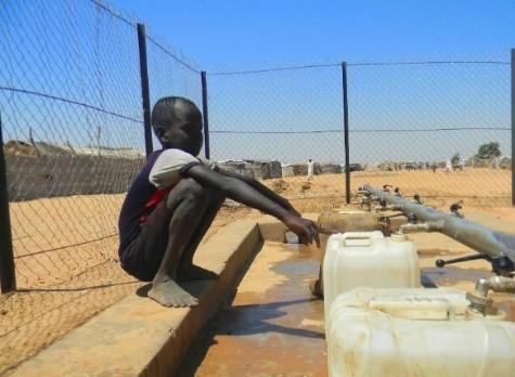 boy fills jerry cans at water point