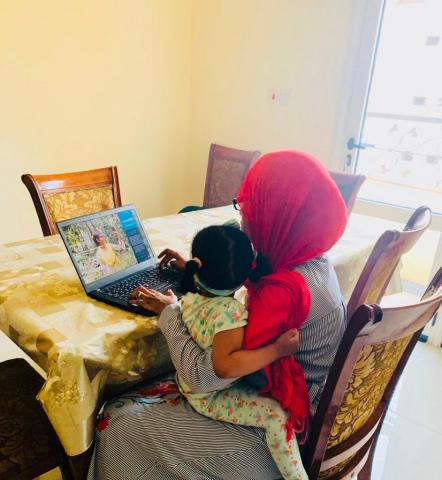 Mother holds child while working on laptop