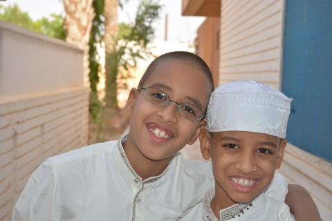 Two boys in white smiling at camera