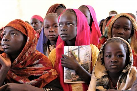 Girl holds book in idp camp