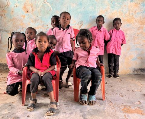 small children in pink uniforms stand and sit in a classroom