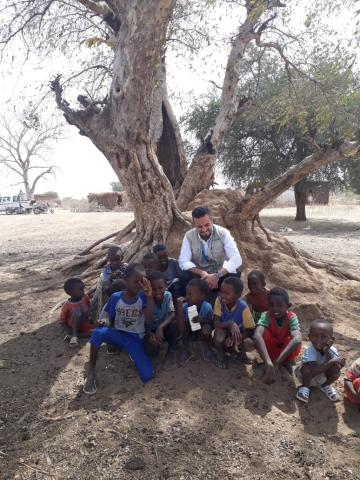 Man smiles underneath tree surrounded by children