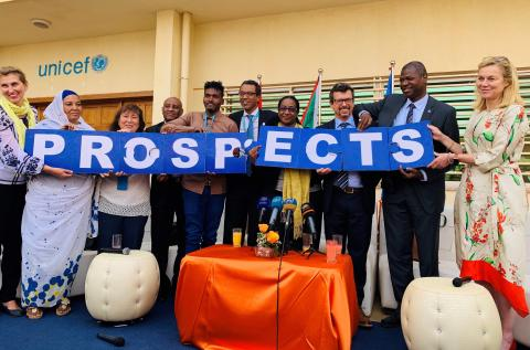 people hold up the letters prospects in blue with white letters