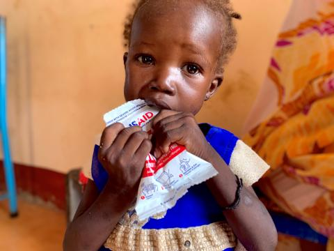 Girl eats nutritional paste with USAID logo