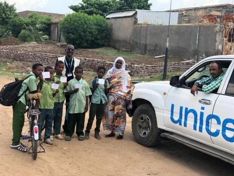 UNICEF driver in car next to vaccinated children