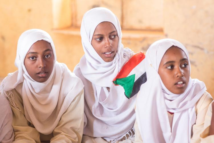Three girls with Sudanese Flag