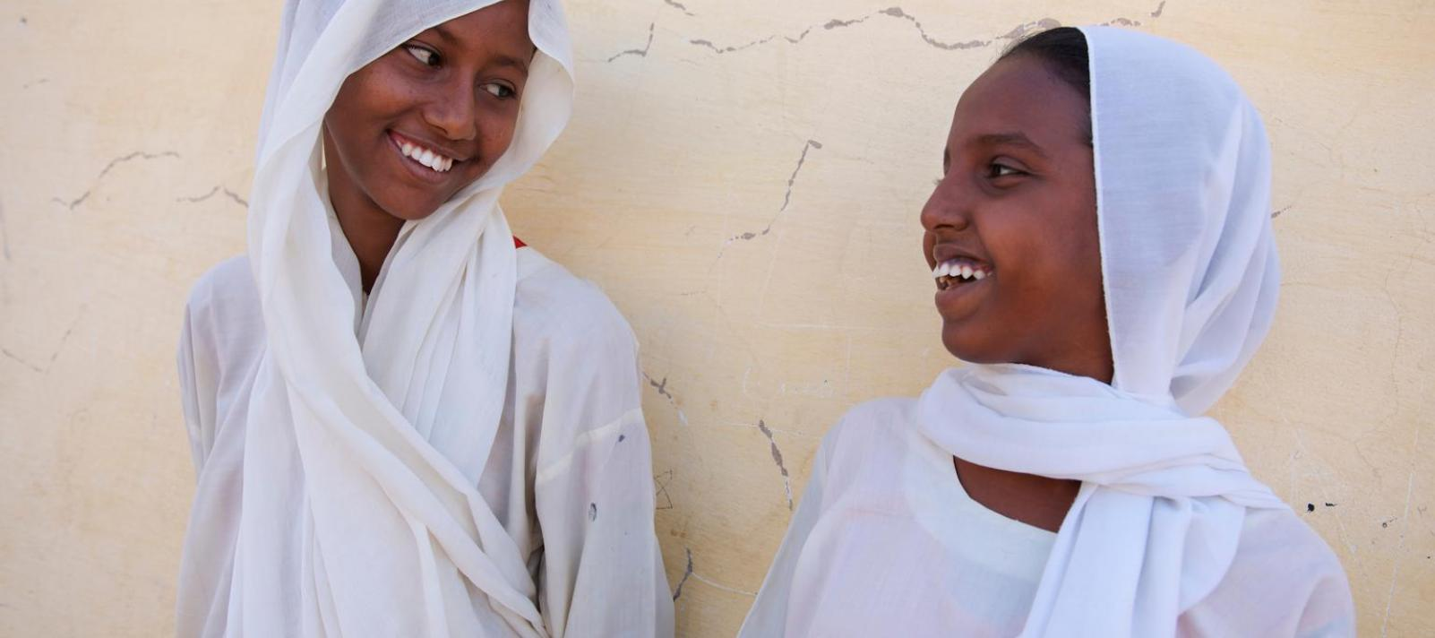 With smiles on the faces, young girls talk to each other standing outside a Child Friendly School called...