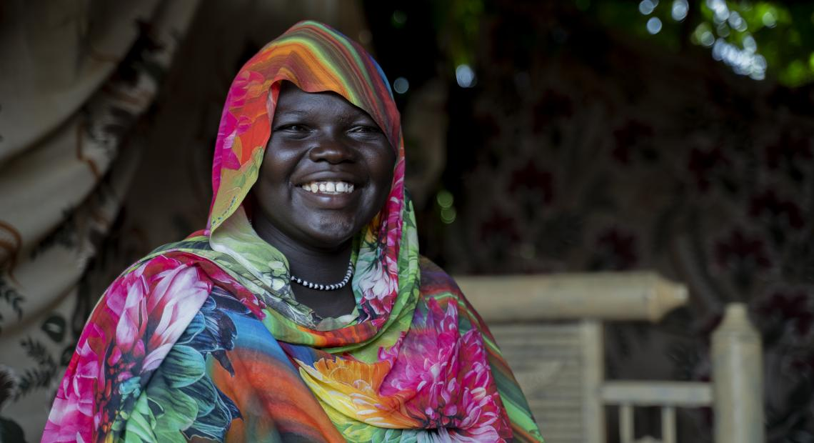 Woman smiles at camera wearing colorful thobe
