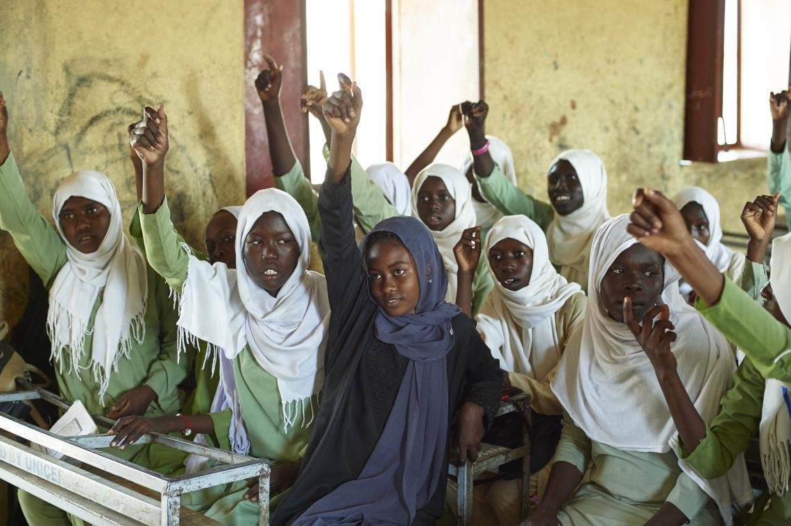 Girls raise their hands in classroom